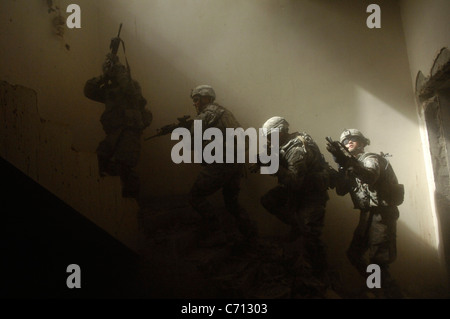 U.S. Army soldiers with Echo Company, 5th Cavalry Regiment, 172nd Infantry Brigade prepare to clear a staircase - Stock Photo