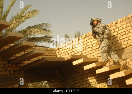 U.S. Army Sgt. Duong Tran moves to a roof top to provide security for other soldiers as they search the roof of - Stock Photo
