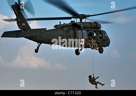 A Soldier dangles from a UH-60 Black Hawk helicopter as he is lowered to the ground during a hoist training exercise - Stock Photo