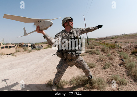 U.S. Army 1st Lt. Steven Rose launches an RQ-11 Raven unmanned aerial vehicle near a new highway bridge project - Stock Photo
