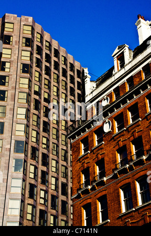a close up image of two buildings with contrasting colors making them stand out against the blue sky. - Stock Photo