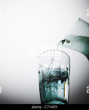 water being poured from a jug into a glass. - Stock Photo