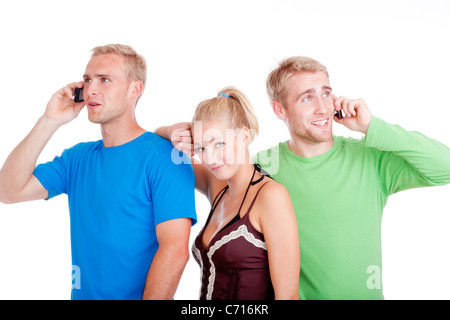 bored young woman standing between two men talking on cell phones- isolated on white - Stock Photo