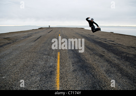 A man jumps in the air at the end of the road and the start of the Bonneville Salt Flats, Utah. - Stock Photo