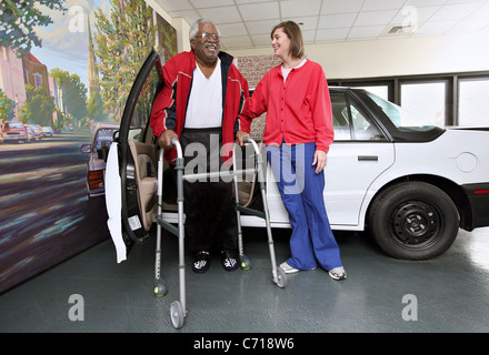 A physical therapist works with a patient on how to get in and out of a car. - Stock Photo