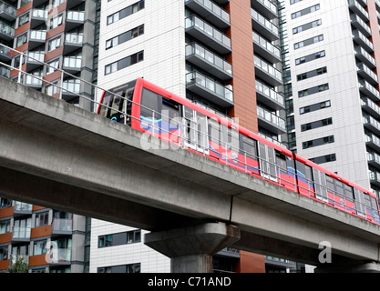 A train on the Docklands Light Railway passes new apartment blocks near East India DLR station on Blackwall Way, - Stock Photo