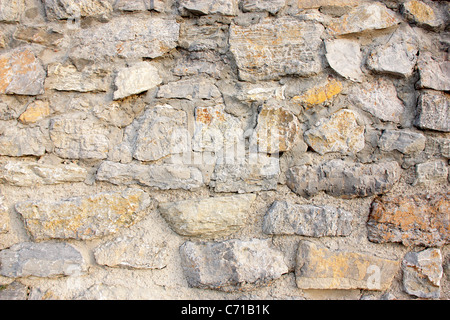 Wall of stones and cement in gray tones with an orange stone in a strong point. - Stock Photo