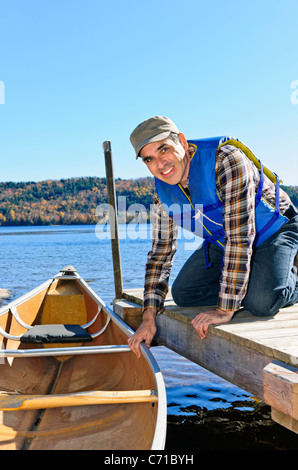 Man holding canoe at dock on Lake of Two Rivers, Ontario, Canada - Stock Photo