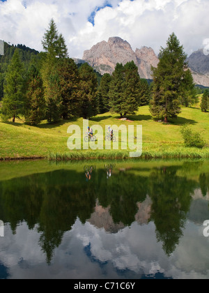 Two mountain bikers are riding a grassy slope along a mountain lake with rock cliffs in the background. - Stock Photo