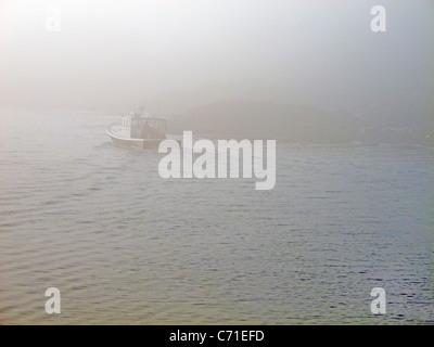 Lobster boat leaving harbor in morning fog - Stock Photo