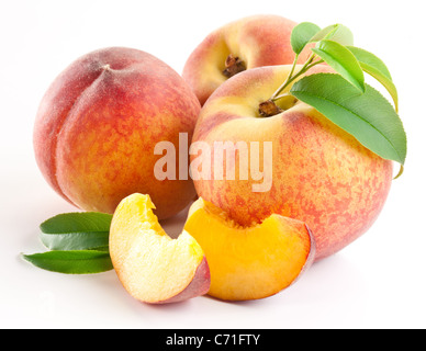 Ripe peach fruit with leaves and slices on white background. - Stock Photo