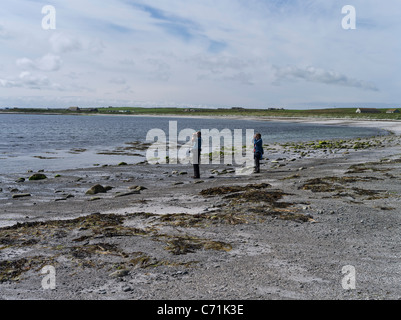 dh  PAPA WESTRAY ORKNEY Two birdwatchers watching with binoculars seashore beach bird watchers - Stock Photo