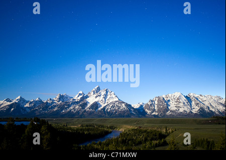 A full moon illuminates Grand Teton National Park with stars in the sky at the Snake River Overlook in Grand Teton - Stock Photo