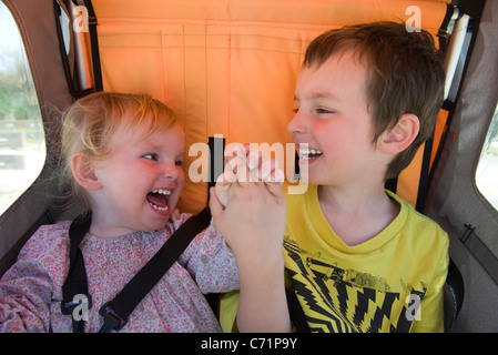 Brother and sister riding together in stroller, laughing and holding hands - Stock Photo