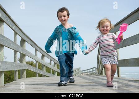Young siblings walking hand in hand on boardwalk