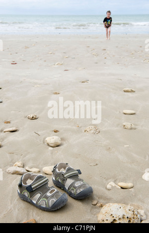 Boy at the beach, focus on sandals in foreground - Stock Photo