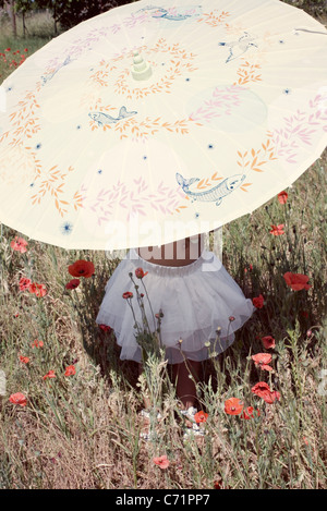 Little girl with parasol in meadow, mid section - Stock Photo