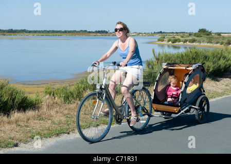 Woman riding along bicycle path with children in bicycle trailer