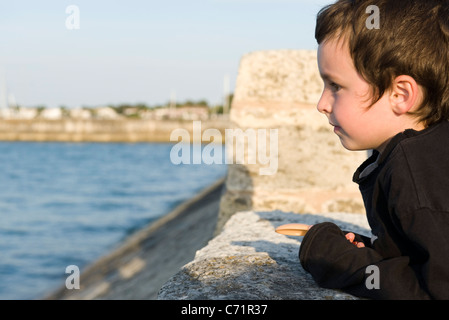 Little boy leaning against stone wall, looking at ocean view - Stock Photo