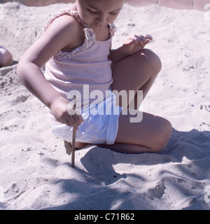 Little girl playing in sand with stick - Stock Photo