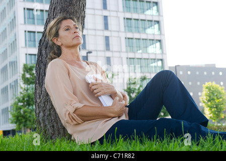 Woman sitting in grass, clutching book - Stock Photo