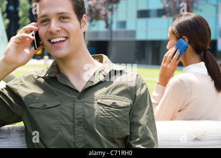 Man talking on cell phone outdoors with cheerful expression - Stock Photo