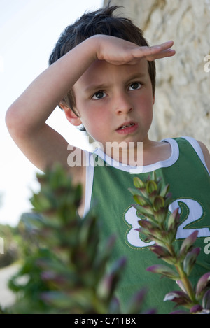 Boy looking at something out of frame, shading eyes with hand - Stock Photo