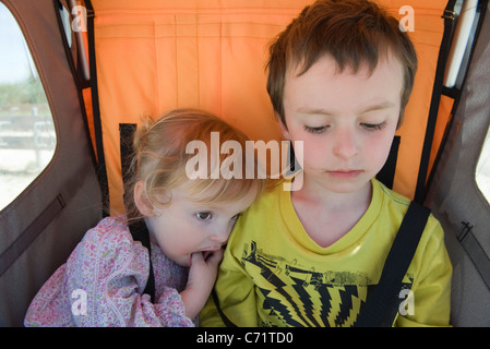 Brother and sister riding together in stroller - Stock Photo