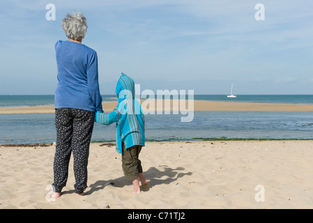 Grandmother and grandson standing together on beach, looking at boat on horizon - Stock Photo