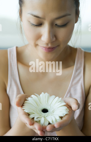 Young woman holding gerbera daisy, portrait