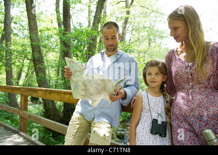Family pausing in woods to consult map - Stock Photo