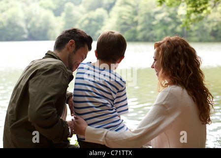 Family by lake, rear view - Stock Photo