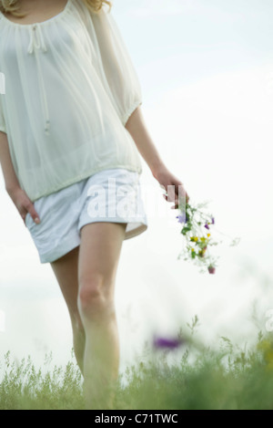 Young woman walking in meadow, carrying bouquet of wildflowers, cropped - Stock Photo