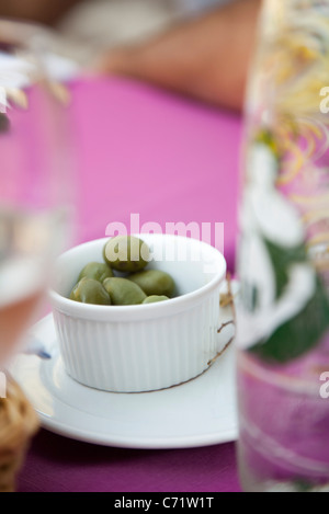 Green olives in ramekin on picnic table outdoors - Stock Photo