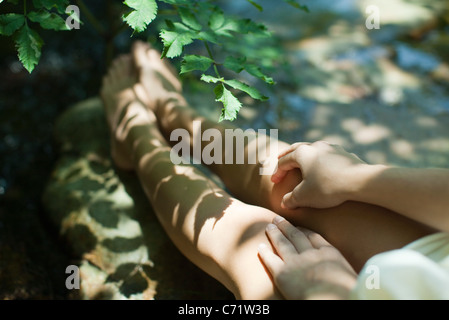 Woman sitting in shadow of tree branches, cropped - Stock Photo