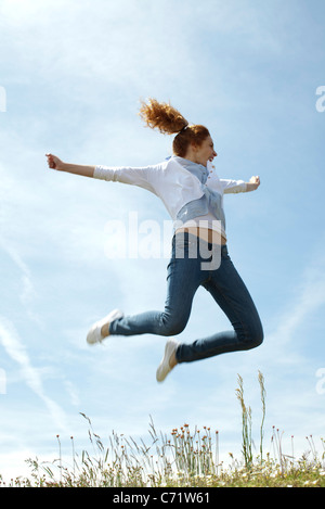 Woman jumping in midair - Stock Photo