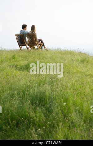 Couple sitting on chairs on top of hill looking at view - Stock Photo