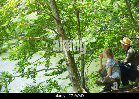 Couple crouching by lake looking at view - Stock Photo