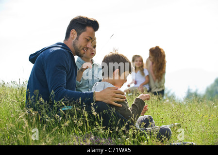 Father talking with young sons outdoors - Stock Photo
