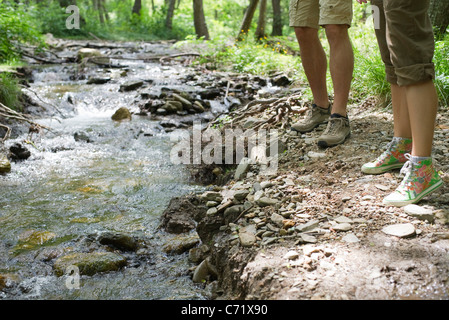 Hikers standing beside stream, cropped - Stock Photo