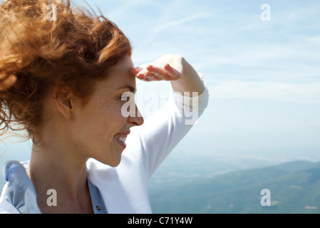 Woman looking at view, shading eyes with hand - Stock Photo