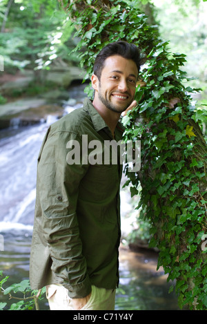 Man standing beside ivy covered tree, portrait - Stock Photo