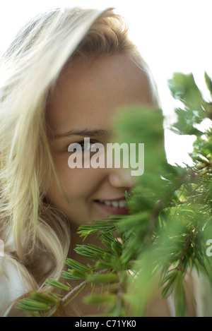 Smiling young woman behind tree branches, cropped - Stock Photo