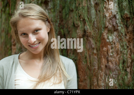 Young woman leaning against tree trunk, portrait