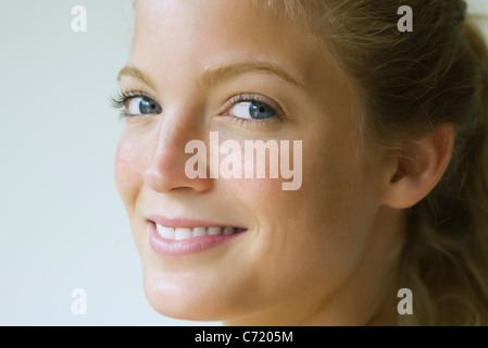Young woman glancing sideways at camera, portrait - Stock Photo