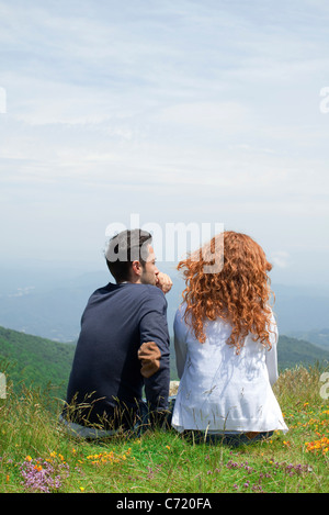 Couple sitting together on hilltop, looking at view - Stock Photo