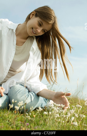 Young woman sitting on meadow with wildflowers - Stock Photo