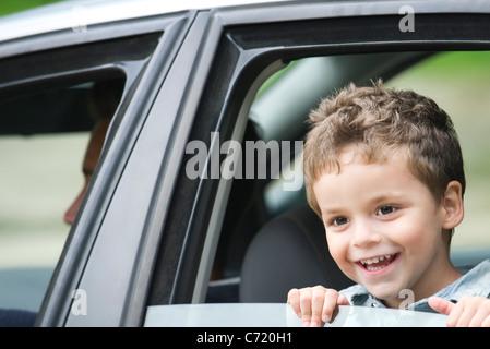 Little boy looking out car window, portrait - Stock Photo