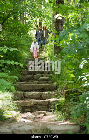 Family walking down stone steps in woods - Stock Photo