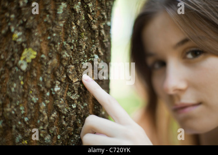 Young woman's finger touching tree trunk, cropped - Stock Photo
